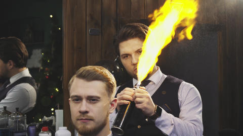 Professional barber working burning fire hair treatment on his client Footage