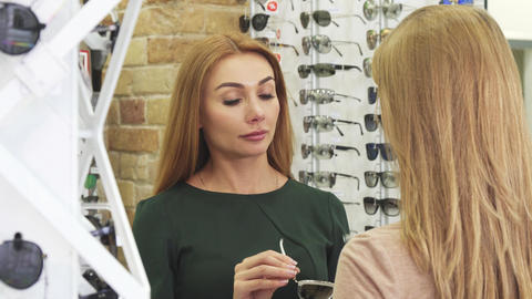 Young beautiful woman trying sunglasses shopping with her friend Footage