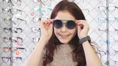 Happy little girl smiling showing thumbs up wearing sunglasses Footage