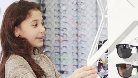 Cute little girl choosing sunglasses from the display at the shopping mall Footage