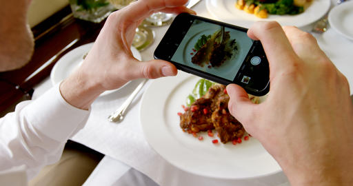 Businessman taking photo of meal with mobile phone 4k Footage