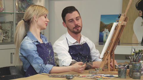 Loving young couple enjoying working on a painting at the Art Studio together Footage