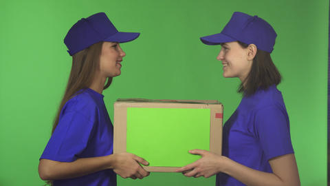 Two cheerful female delivery service workers smiling holding cardboard box Footage