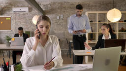 Young serious businesswoman is talking on phone in office, writing down, office Footage
