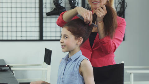 Cute happy little her getting her hair done by a hairdresser at the beauty salon Footage