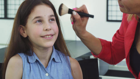 Close up of a pretty little girl smiling while her mom applying makeup on her Footage