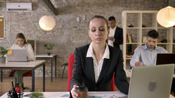 Young beautiful business woman is typing on laptop in office, drinking coffee Footage