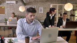 Young tired businessman is working in office, tapping on laptop, discussion on Footage