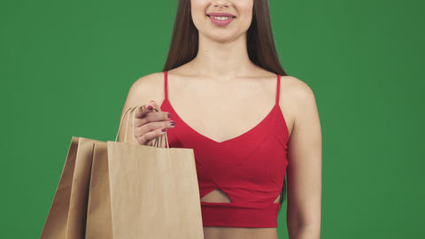Cropped studio shot of a woman smiling holding shopping bags showing thumbs up Live Action