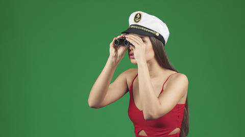 Stunning woman in a sailor cap smiling after looking away through binoculars Footage