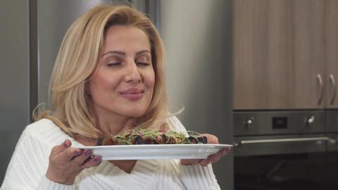 Close up of a gorgeous woman smelling delicious vegetarian salad ビデオ