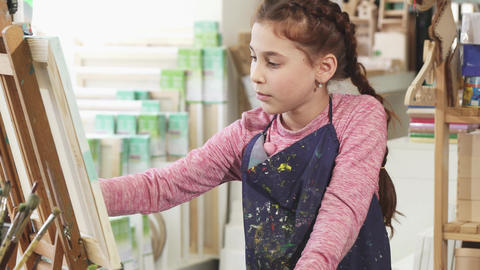 Beautiful little girl painting on the easel using oil paints at the art studio Footage