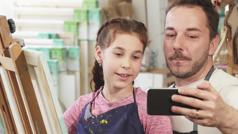 Happy father and daughter taking selfies at art studio while painting Footage