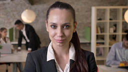Young charming businesswoman is watching at camera in office, smiling, her Footage