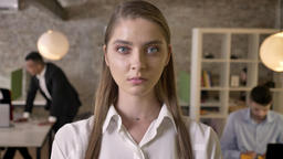 Young confident businesswoman is staring at camera in office, her colleagues are Footage