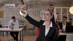 Young businesswoman is making selfie on smartphone in office, her colleagues are Footage