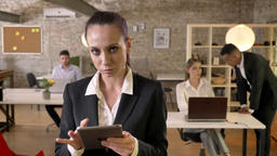 Young serious businesswoman is tapping on tablet in office, watching at camera Footage