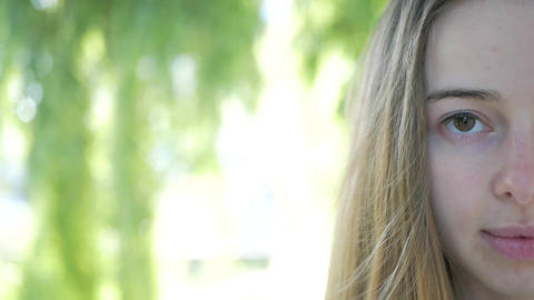 closeup portrait of beautiful girl looking at camera. Half her face Live Action
