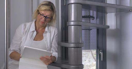 Adult woman sitting on stairs with tablet Footage