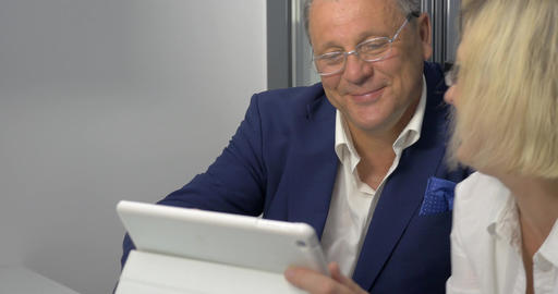 Mature man and woman doing business with tablet PC Footage
