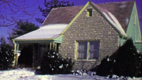 1964: Quaint brick facade bungalow suburban house garage driveway pan Footage