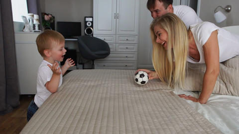Dad and mom play with the boy on the bed with the ball Footage