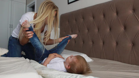 Mom and son are playing on the bed in a bright bedroom, a boy of two years Footage