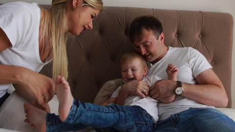 Loving parents play with their son on the bed laughing and smiling in the Footage