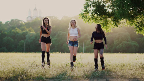 Three girls in boots with springs running through the summer Park at sunset Footage