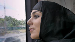 Young muslim woman in hijab is watching in rainy window in bus, transport Footage