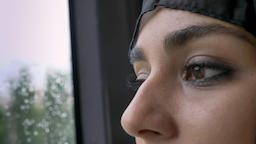 Young muslim woman's in hijab eyes is watching in rainy window in bus, weather Footage