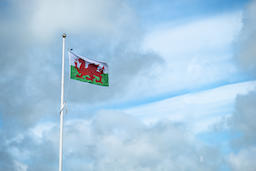 Flag of Wales on the mast with clouds in the background Photo