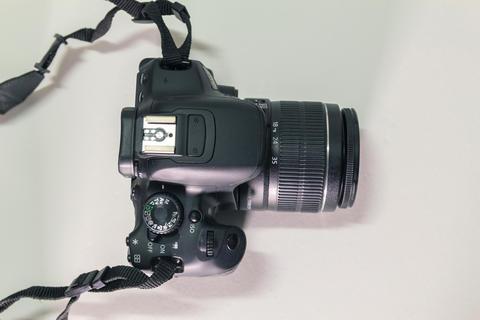 Closeup top view of modern black DSLR camera on white background フォト