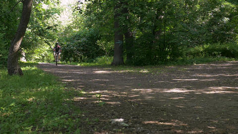 Man on a bicycle in summer in a park. slow motion ビデオ