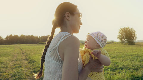 Cheerful mother and her baby girl on summer field in the evening Footage