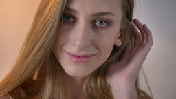 Young blonde women with blue eyes looking in camera and touching her hair Footage