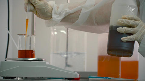 Chemist with pipette add liquid from a bottle into a flask on electronic scales Footage