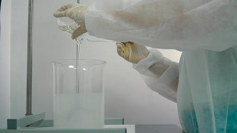 Chemist pouring gel into container with mixing liquid in pharmaceutical blender Live Action