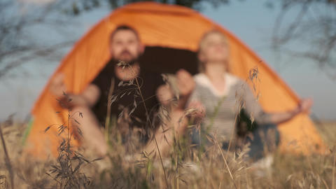 A couple on a background is meditating in front of a tent, breathing calm and Live Action