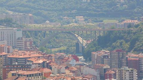 Miraflores Bridge in Bilbao rising over building rooftops, Spain architecture Footage