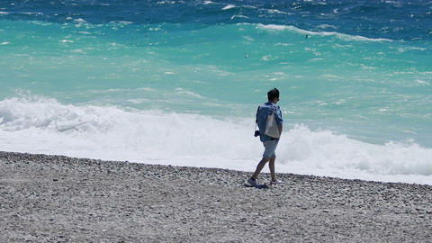 Lonely man walking along coast, enjoying sound of waves and pleasant breeze Footage