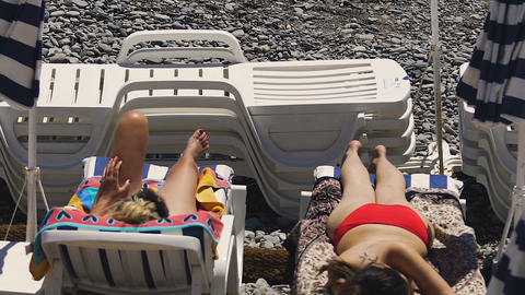 Two attractive women spending holidays relaxing and sunbathing on seashore Footage