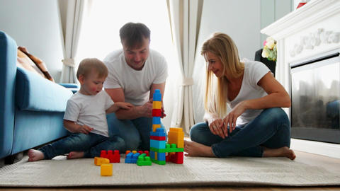 Happy family dad mom and baby 2 years playing lego in their bright living room Footage