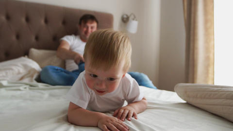 Dad plays with his son lying in krvoi, laughter and smiles Live Action