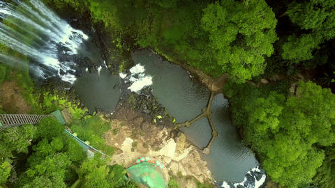 flycam turns round above waterfall running into gorge Footage