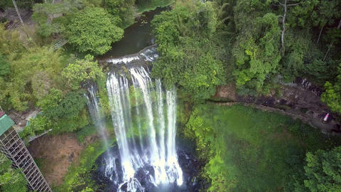 drone goes down to waterfall among lush jungle Live Action