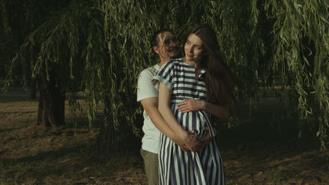Loving parents expecting baby embracing in park Footage