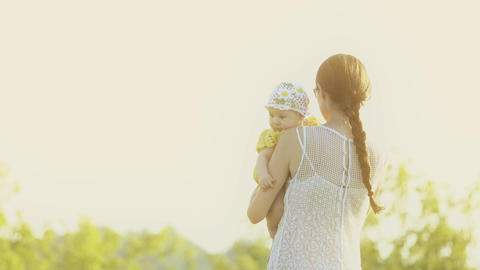 Mother holding her baby girl on summer field in the evening Footage