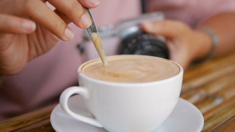 Slow motion hand of woman using spoon to mix the coffee in the cup GIF