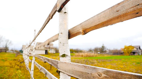 The camera moves along the wooden fence. Slow motion. Autumn landscape Footage